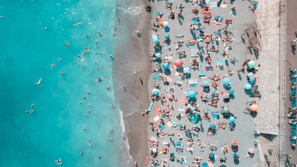 aerial shot of beach and ocean and people enjoying the sun symbolizing the importance of fresh and effective sunscreen as part of K-beauty influenced holistic skincare habits and rituals