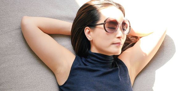 Woman with arms folded behind head showing off her underarms prominently symbolizing the importance of an underarm detox as part of K-beauty influenced holistic skincare habits