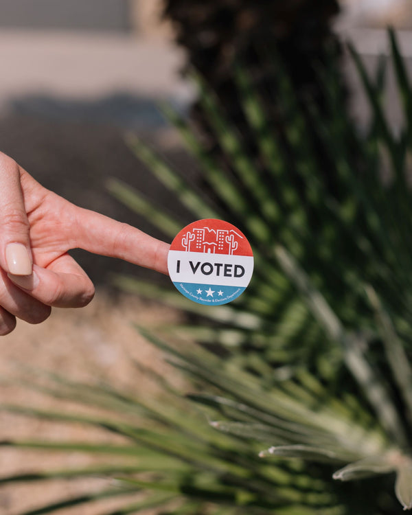 woman's-finger-holding-up-I-voted-sticker-symbolizing-the-importance-of-voting-and-self-care-skincare-rituals-during-election-season-as-part-of-K-beauty-influenced-holistic-skincare-habits-and-rituals