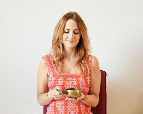 woman in red dress symbolizing Valentine's day with meditation sound bowl in hand engaging in a loving-kindness meditation as part of K-beauty influenced holistic skincare habits and rituals