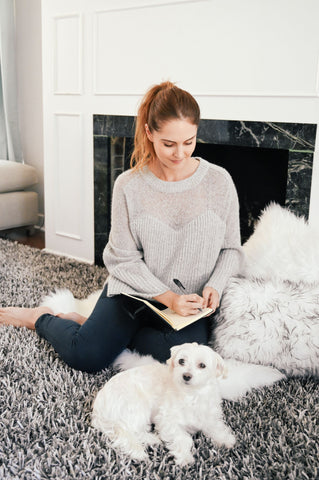 woman journaling her new year's skincare resolutions in front of fire place with white puppy as part of K-beauty influenced holistic skincare habits and rituals
