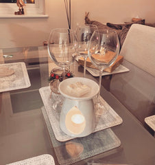 white wax melter on dinning table with wine glasses and four cubes of soy wax