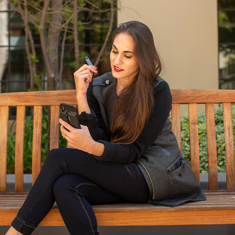 Woman sitting on bench, holding Fluux case and vape, looking at her phone.