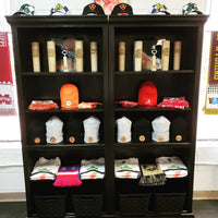 An in store display that features baseball bat beer mugs, hats socks, scarves, shirts and art from a local artist.