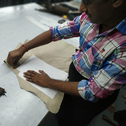 man cutting leather pattern at factory in new delhi, india