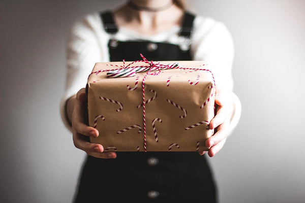 Person holding gift wrapped in kraft paper