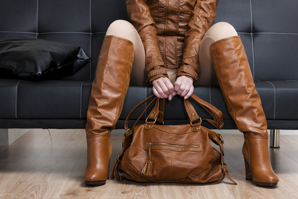 Women wearing cream leggings with brown boots, a brown handbag and matching brown leather jacket.