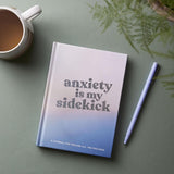 Anxiety Is My Sidekick journal with cup of tea, houseplant and pen