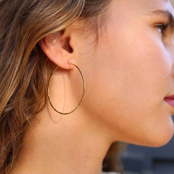 Model wearing Hand made in London Brooke Gregson 18k gold hammered hoop earrings