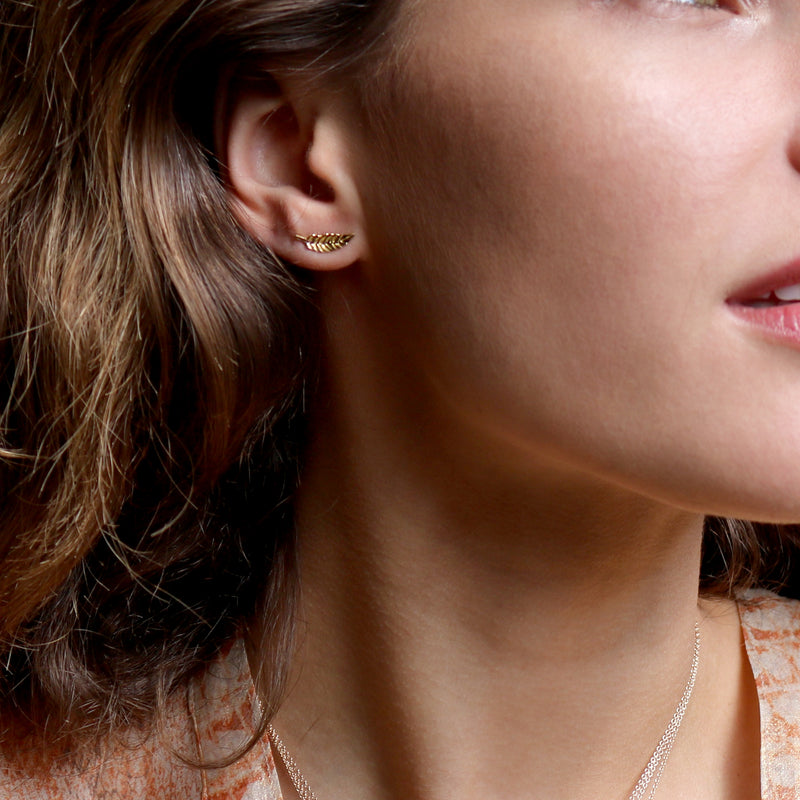 Model wearing Hand made in London 18k gold carved leaf earrings