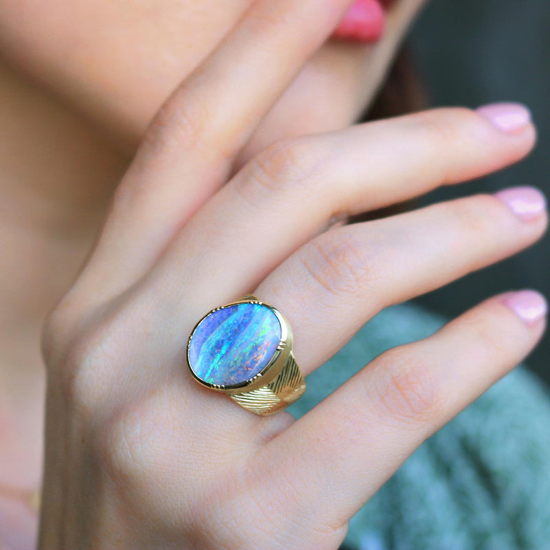 Model wearing Hand made in London Brooke Gregson 18k gold engraved boulder opal ring