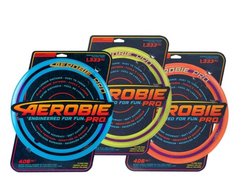 Three aerobie discs in blue, yellow and orange from left to right sit in their black packaging on a neutral background.