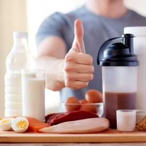 Man giving a thumbs up in the center of different protein sources, milk, eggs, fish, meat, protein powder and a protein shake