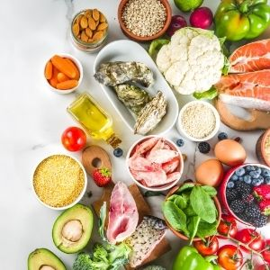 Healthy foods including meats, vegetables, nuts, fish and fruits laid out on table in small bowls