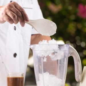 Hand spooning ice into a blender