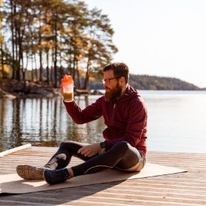 Man sitting on yoga mat on a jetty by the lake looking at a half finished protein shake