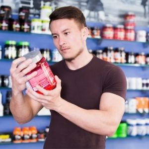 Man looking at nutritional label on a protein powder supplement