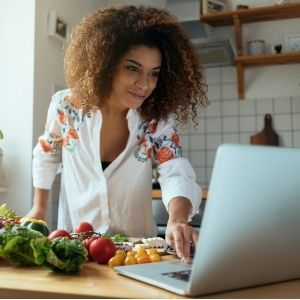Woman looking at recipes on computer and preparing to make a meal