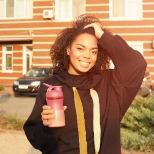 Woman standing outside pulling her hair back with one hand and holding a shaker bottle with the other