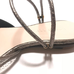 "Detail of the elastic ankle strap of All Black pointed toe shoes with a heel of 1/4"" height  in the color of silver"