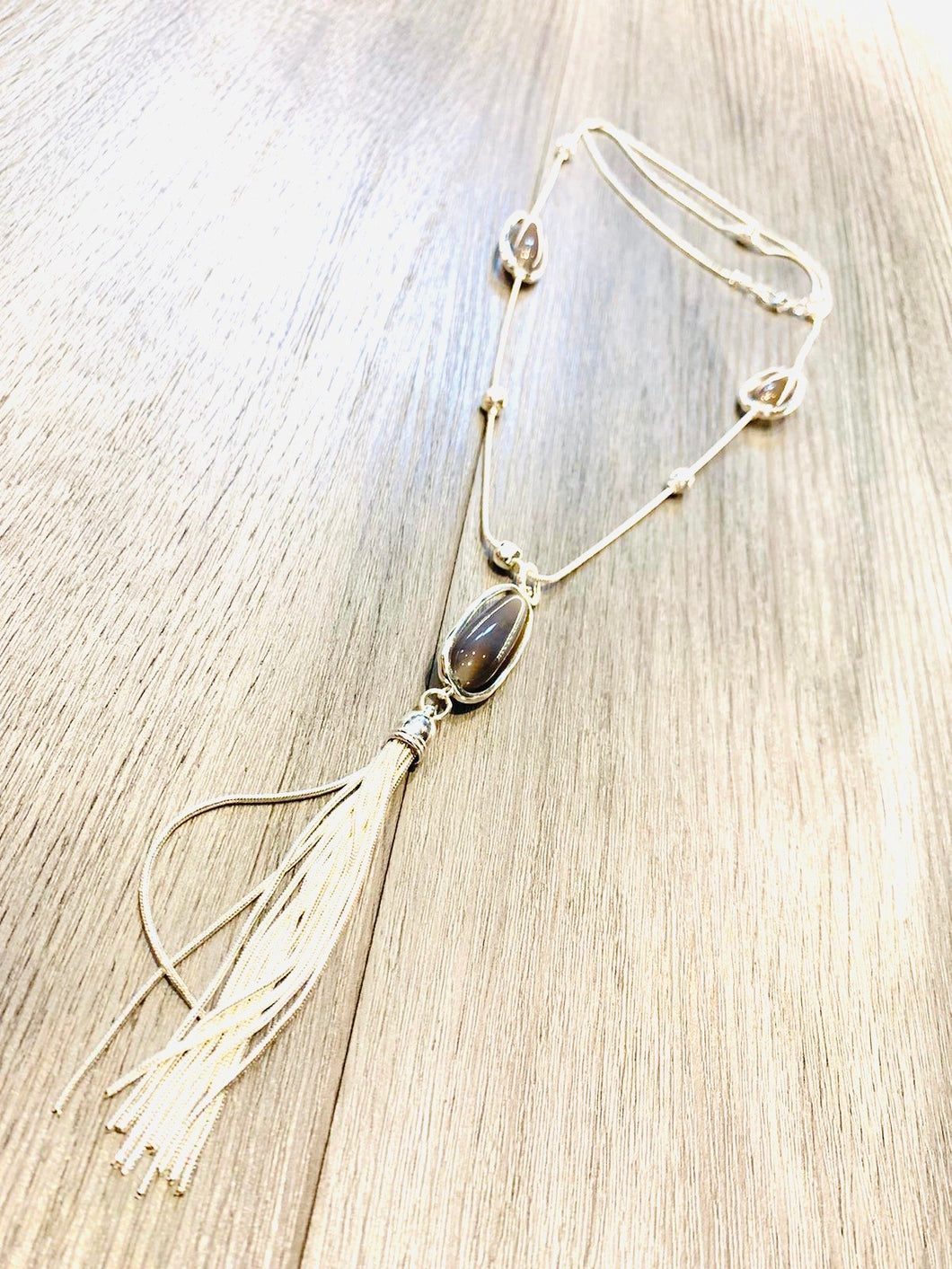 Grey stone and tassel pendant on a long snake chain