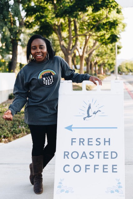 "Girl posing in a Wild Goose Rainbow gray long sleeve, near our ""Fresh Roasted Coffee"" sign."