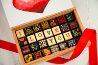 28 gourmet dark chocolate art bonbons of assorted flavors and the words I Love You. Handcrafted with 70% Venezuelan Cocoa.