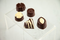 Dark and white chocolate bonbons of unique shapes filled with assorted flavors and handcrafted with High-Quality White Chocolate and 70% Venezuelan Cocoa, the best of the world.