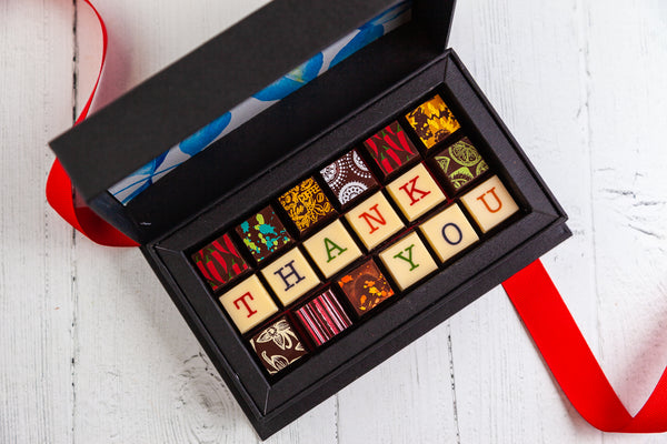 18 gourmet dark chocolate art bonbons and the words Thank You. Handcrafted with 70% Venezuela Cocoa.