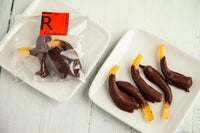 Organic glacé orange peels dipped in dark chocolate, made with 70% Venezuelan Cocoa. Suitable for vegans, dairy, and gluten-free. 40 gr of addictive flavors.