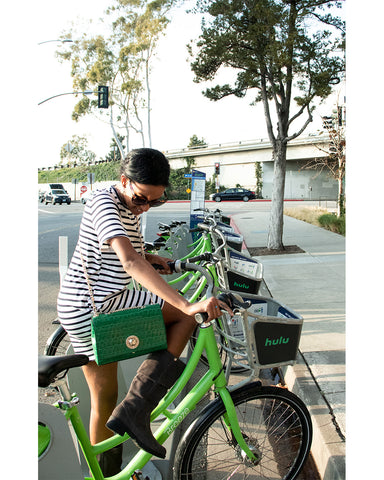 woman with green handbag getting on green bike