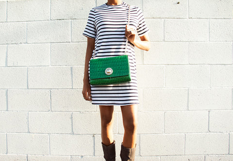 woman standing in front of white wall with green crossbody bag