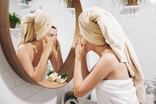 a woman exfoliating her face | The Guilty Woman