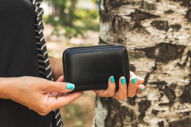 woman holding small leather wallet_ The Guilty Woman