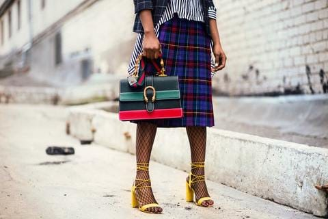 woman holding Gucci bag wearing a plaid skirt