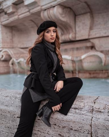 a woman sitting next to a fountain and wearing all black