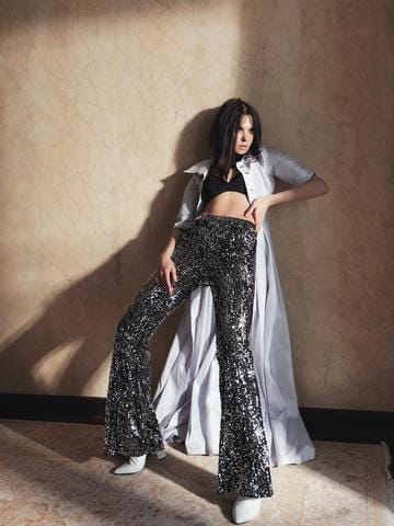 woman standing against wall in sequined pants