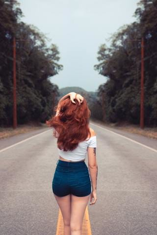 woman with red hair and short shorts turned around