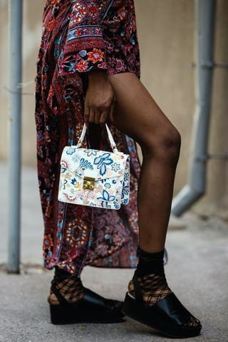 woman holding white floral bag