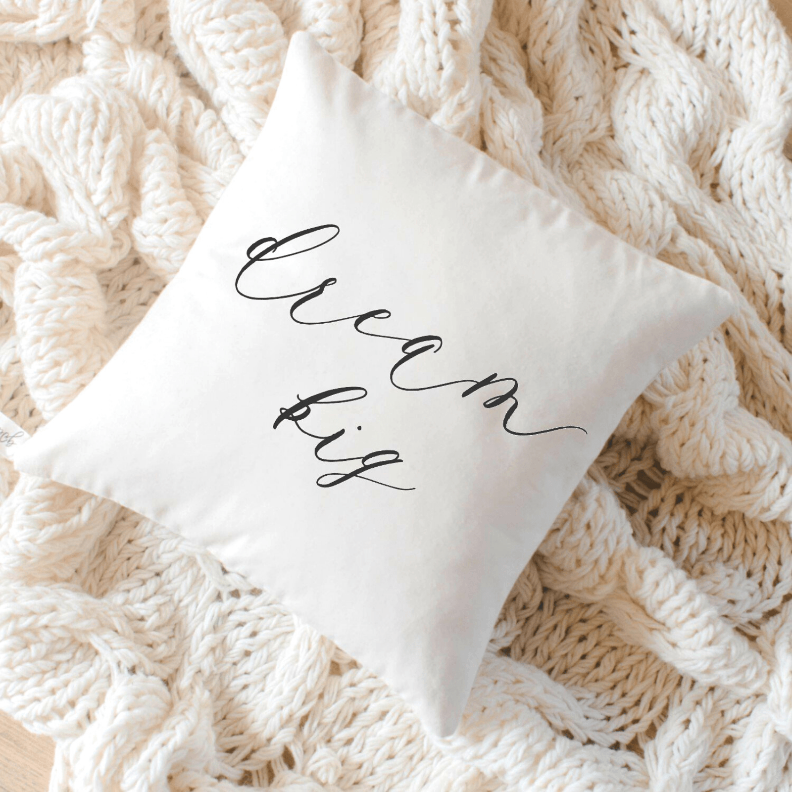 """Dream Big"" pillow on white blanket"