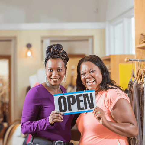 Two women holding up 'open' sign