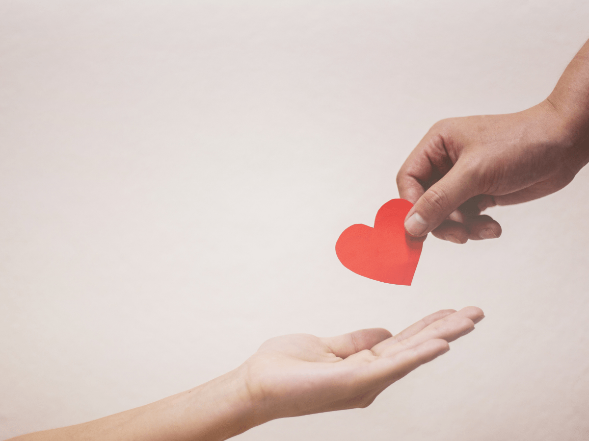 Paper heart being transferred from one hand to another
