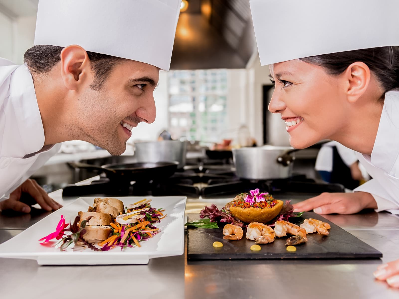 Two chefs leaning over, looking at each other, with their plates of food in front of them