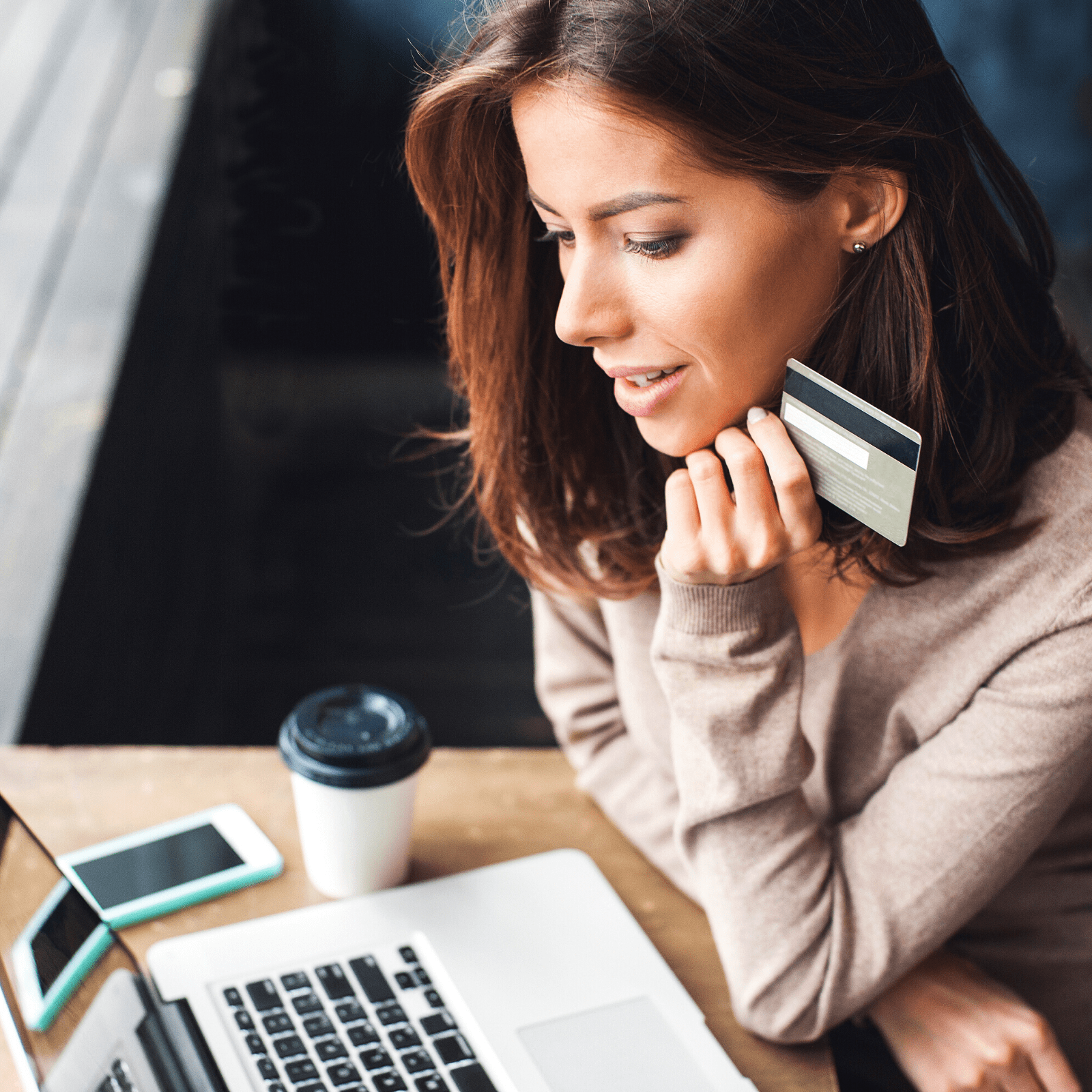 Woman looking at her laptop with credit card in hand