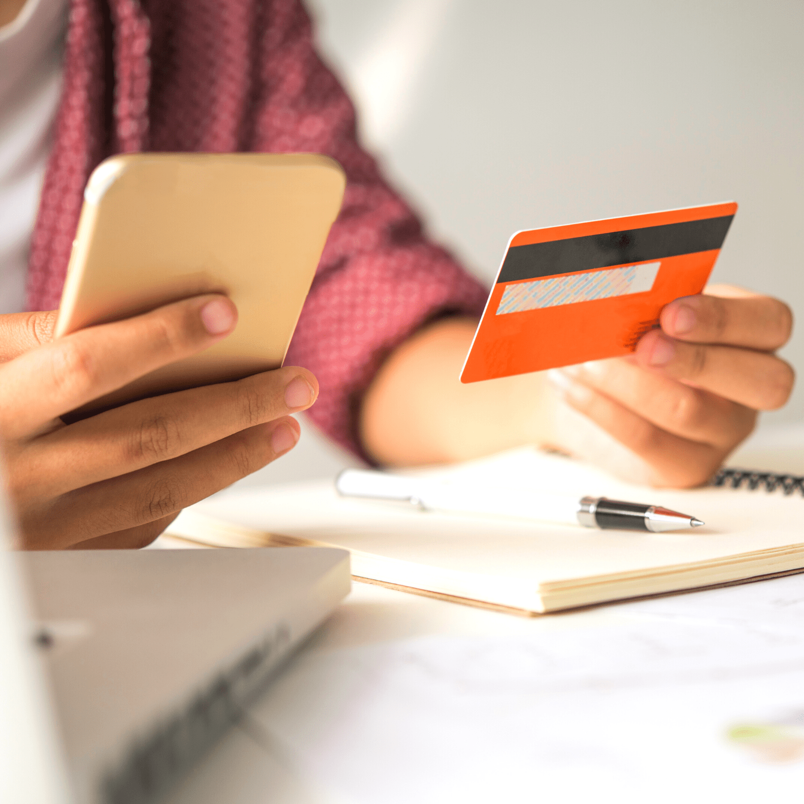 Woman with phone in right hand and credit card in left