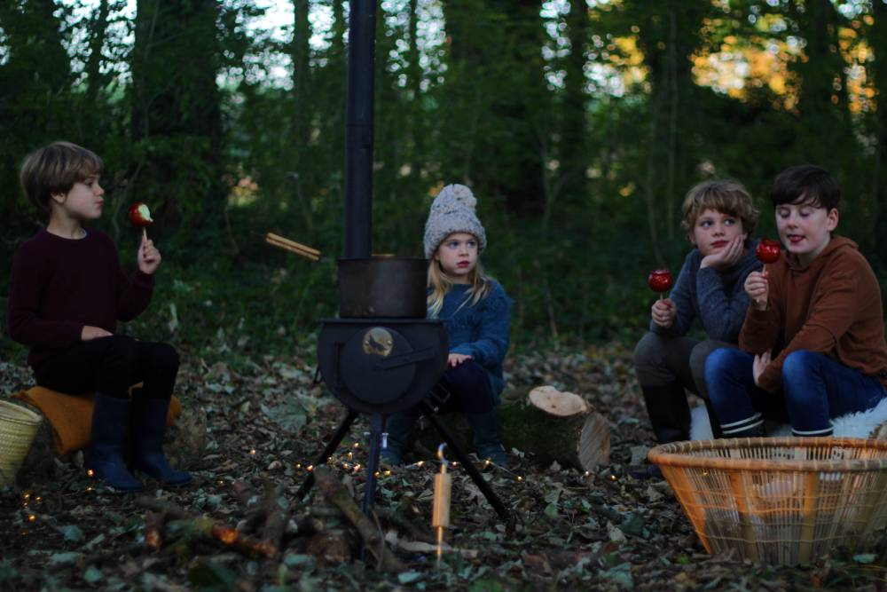 Children eating toffee apples sat around Anevay Frontier wood burning stove