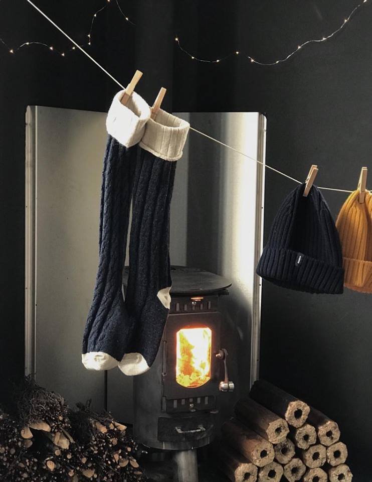 Finisterre accessories hanging infront of an Anevay woodburning stove