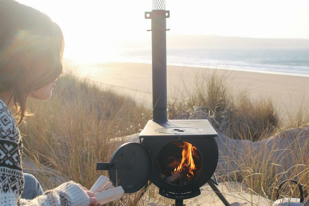 The Girl Outdoors cooking outdoors on an Anevay portable woodburning stove