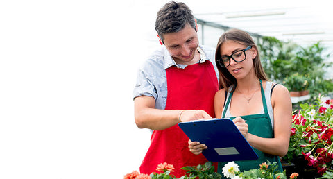 Two people with gardening supplies and clipboard