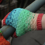 Top-down view of textured fingerless mitt that shifts from cream to green to blue with coral cuffs.